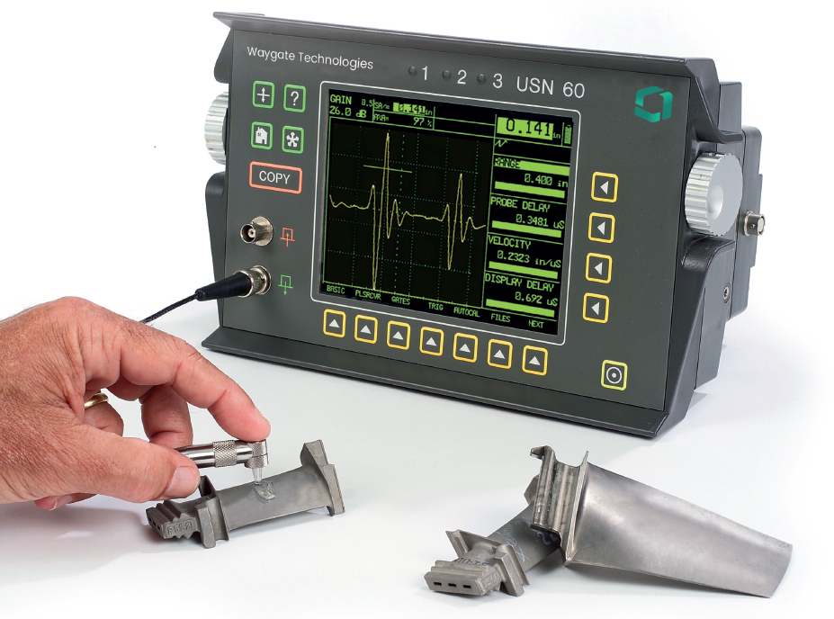 man using USN 60 ultrasonic flaw detector to inspect small metal piece