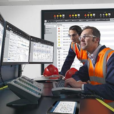 Two workers safety vests and protective glasses looking at multiple screens